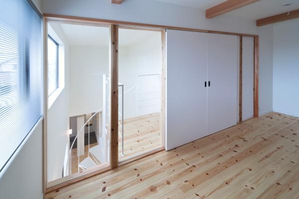 『金石の家』プライバシーを守りながら開放的に暮らす家の部屋 ガラス張りの窓と白い引き戸の洋室