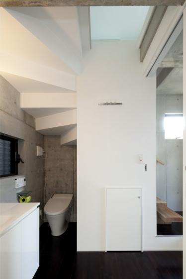 『目黒の家』シンプル&クールな住まい (階段下のトイレ)