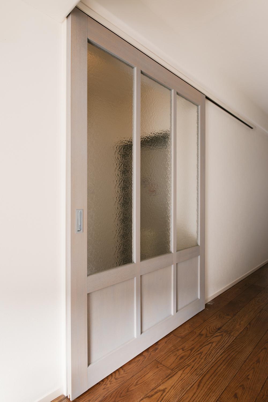 K邸・最大限の空間を確保した上質なインテリアの写真 LDK入口-すりガラスの造作引き戸