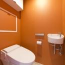 M邸・子供も大人も楽しく安心に暮らす家の写真 オレンジ壁のトイレ