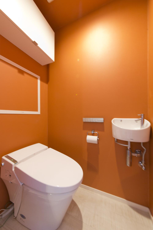 M邸・子供も大人も楽しく安心に暮らす家の部屋 オレンジ壁のトイレ