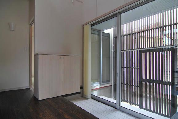 『赤備えの家』プライバシーを守る住まいの部屋 ガラス戸の開放的な玄関