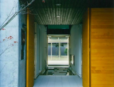 庭まで見通せる玄関 (『空を臨む家』光と風を取り入れる緑豊かな住まい)