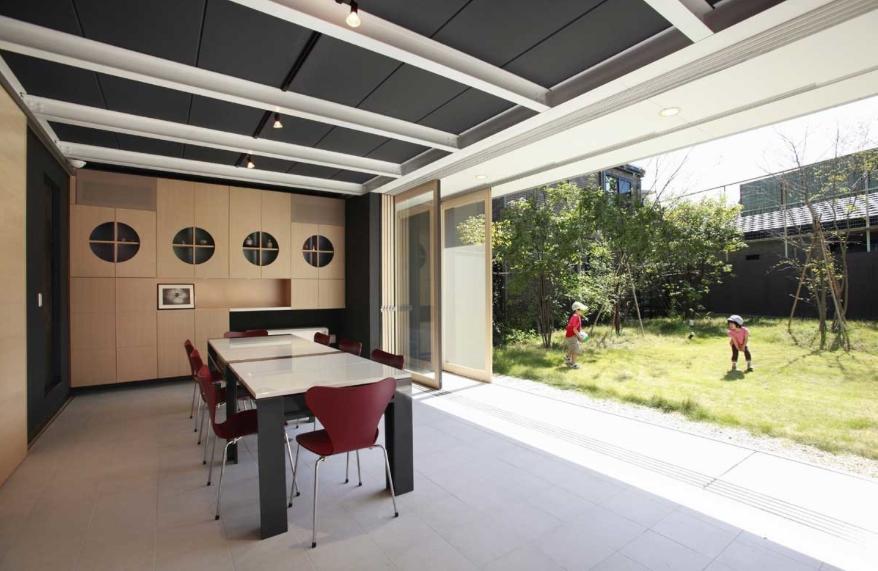 『空を臨む家』光と風を取り入れる緑豊かな住まいの部屋 全面開放できる1階会議室