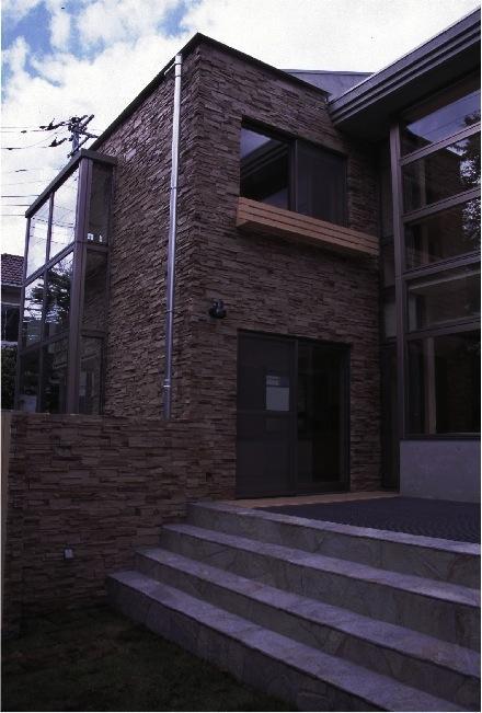 『桜・山・石』優しい光の集まる石貼りの家の写真 石貼りの家外観-2
