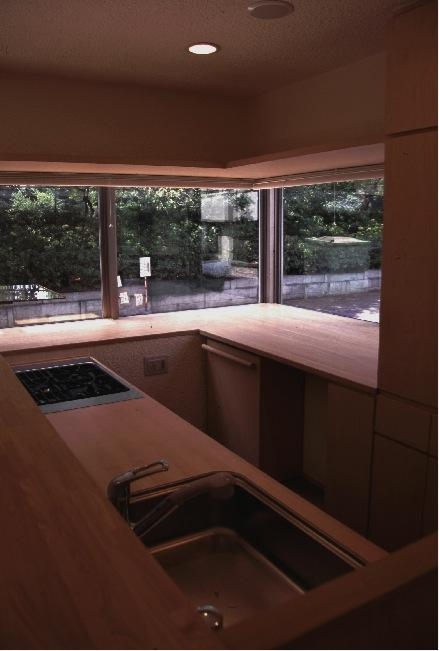 『桜・山・石』優しい光の集まる石貼りの家の写真 コーナーウィンドウのある明るいキッチン