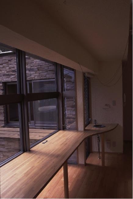 『桜・山・石』優しい光の集まる石貼りの家の部屋 柔らかな光の差し込むワークスペース