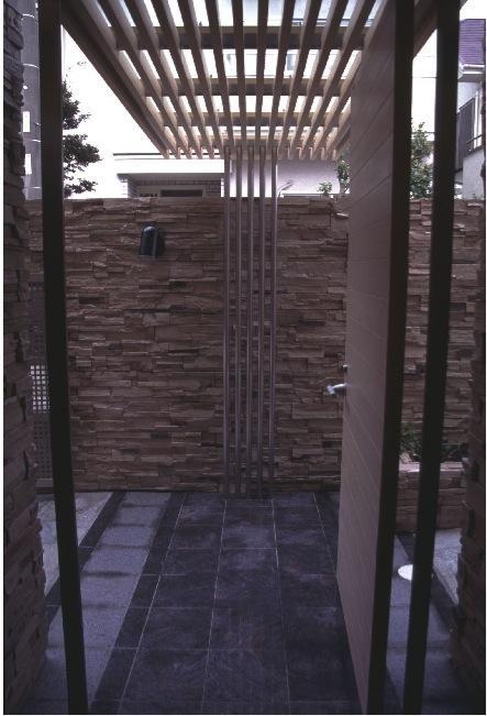『桜・山・石』優しい光の集まる石貼りの家の写真 天井ルーバーの玄関ポーチ