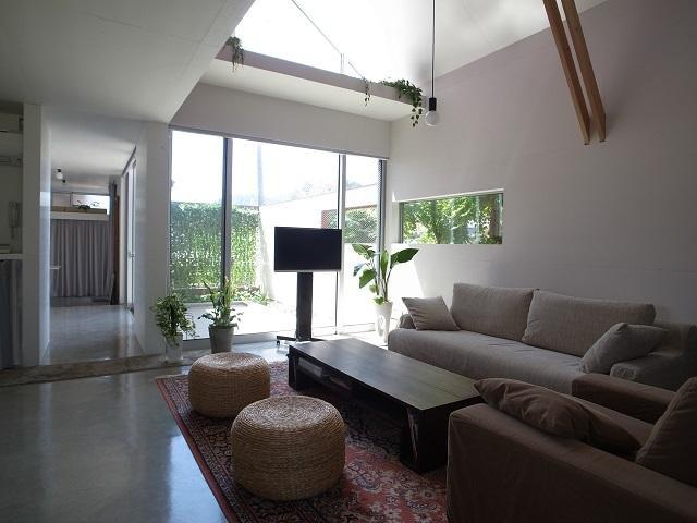 『青海町の家』スタイリッシュなアトリエ兼用住宅の写真 明るい吹き抜けリビング-1