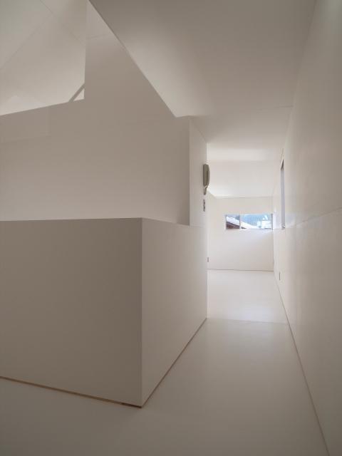 『青海町の家』スタイリッシュなアトリエ兼用住宅の写真 白で統一された2階ホール