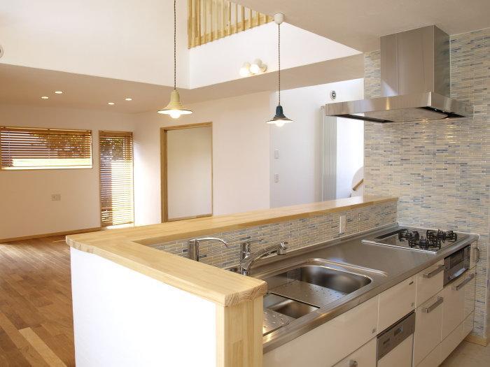 『コダマノイエ 』家族をつなぐ柔らかな風合いの住まいの写真 ブルーモザイクタイルが爽やかなキッチン