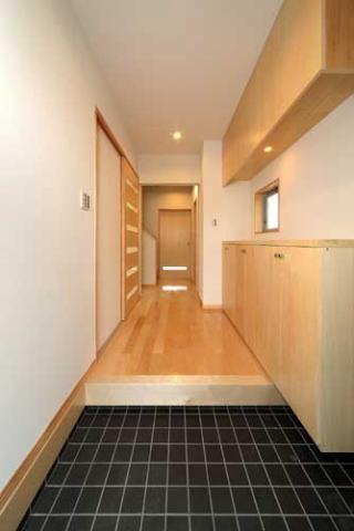 『キュービック・デッキ』リゾート風住宅にダイナミックリフォームの写真 黒いタイル床の玄関ホール