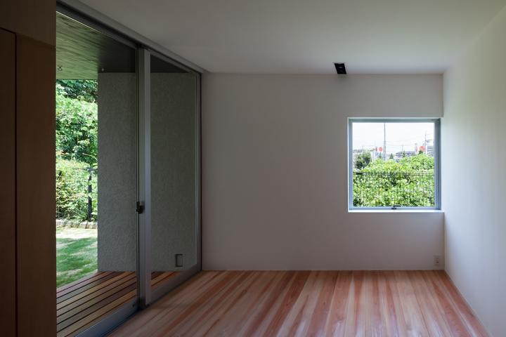 『西向きの家』デッキテラスがつなぐ住まい (正方形窓が景色を切り取る寝室)