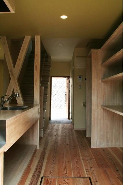 『イシブロノイエ』木に囲まれた落ち着いた空間の写真 キッチンより玄関を見る