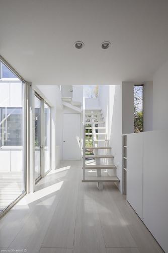 『蛭根の丘』白基調のスタイリッシュな住まいの部屋 玄関より階段を見る