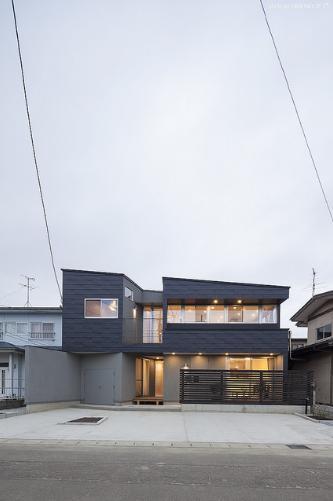 『牛島の二世帯住宅2 』2階をワンルームとする大胆なプランの写真 黒いガルバリウム鋼板の外観