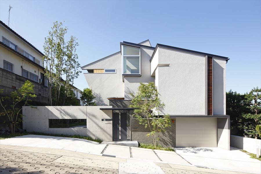 『多層一体の家』立体的ワンルーム空間の住まいの部屋 傾斜に建つ白い外観