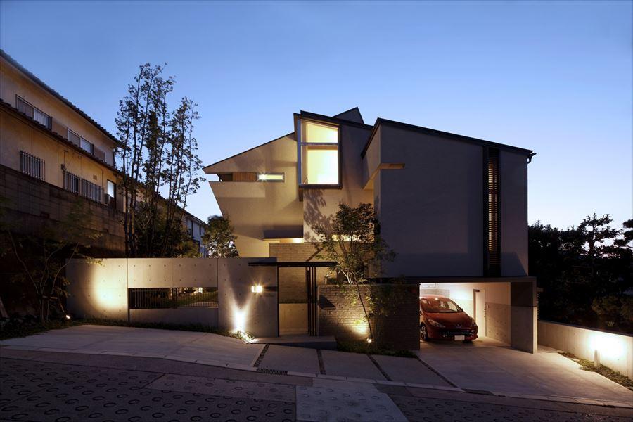 『多層一体の家』立体的ワンルーム空間の住まいの部屋 傾斜に建つ外観-夜景