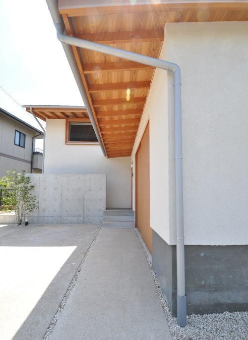 『可児の家』開放感溢れるナチュラルな住まいの部屋 深い庇の下のアプローチ
