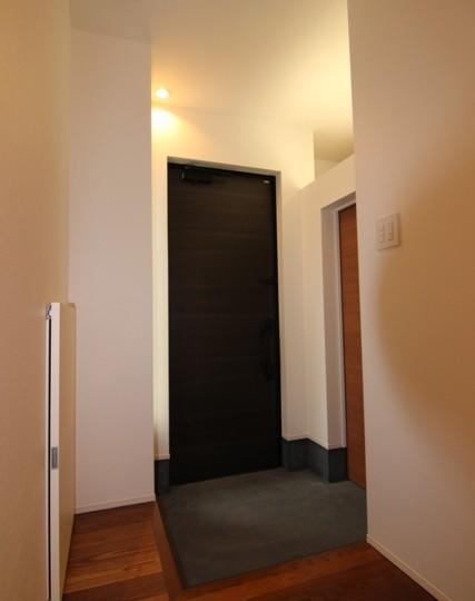 『LX2 house』2つのリビングがある共働き・子育て世帯の理想の家の写真 黒いドアがアクセントの玄関