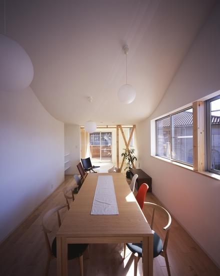 『坂の南の家』曲面天井のある立体的な構成の部屋 優しい光の差し込むダイニング