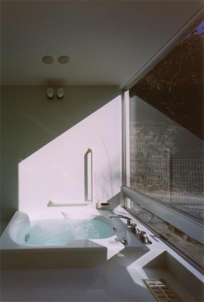 『柳井の家』ロケーションを最大限に生かした住まいの写真 ガラス張り窓のバスルーム