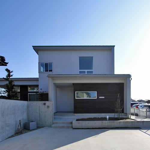『津幡町の家2』共有庭に面した屋外リビングのある住まいの部屋 シンプルモダンな外観