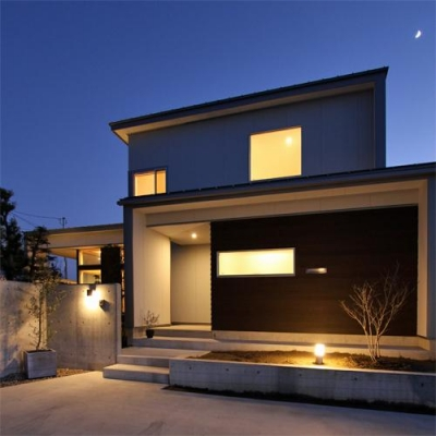 『津幡町の家2』共有庭に面した屋外リビングのある住まい (シンプルモダンな外観-夜景)