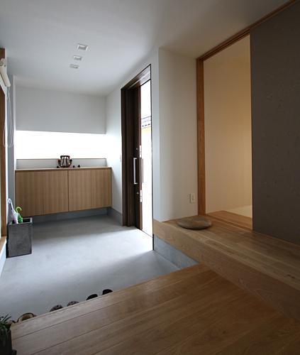 『津幡町の家2』共有庭に面した屋外リビングのある住まいの部屋 開放的で明るい玄関