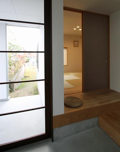『津幡町の家2』共有庭に面した屋外リビングのある住まいの部屋 玄関より和室を見る