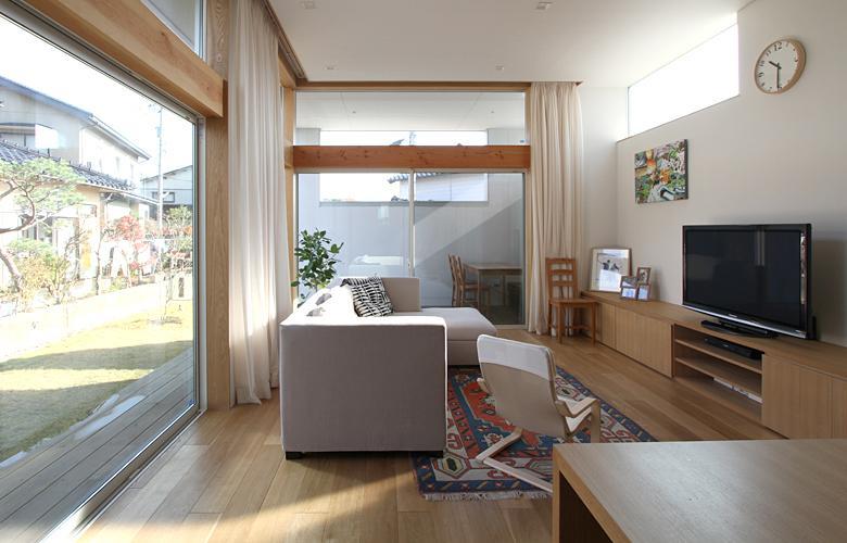 『津幡町の家2』共有庭に面した屋外リビングのある住まいの部屋 ガラス張りの明るいリビング