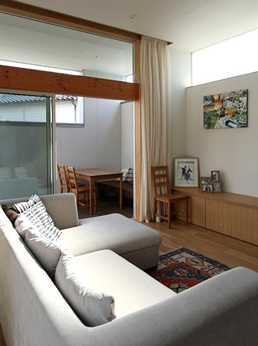 『津幡町の家2』共有庭に面した屋外リビングのある住まいの部屋 屋外デッキにつながるリビング