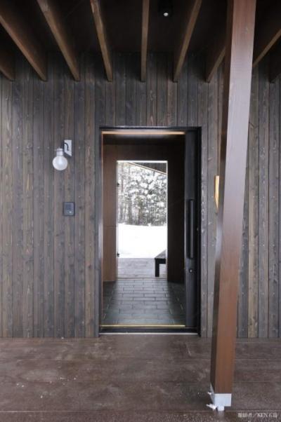 1階テラスより玄関を見る (『丘の家』深みのある木目が落ち着いた空間を演出)