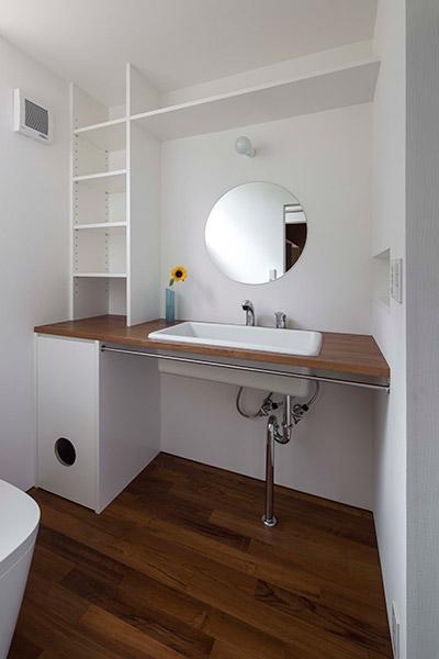 『よみうりランド前の家』仕事と主婦業の両立がしやすい住まいの写真 丸鏡のシンプルな洗面スペース