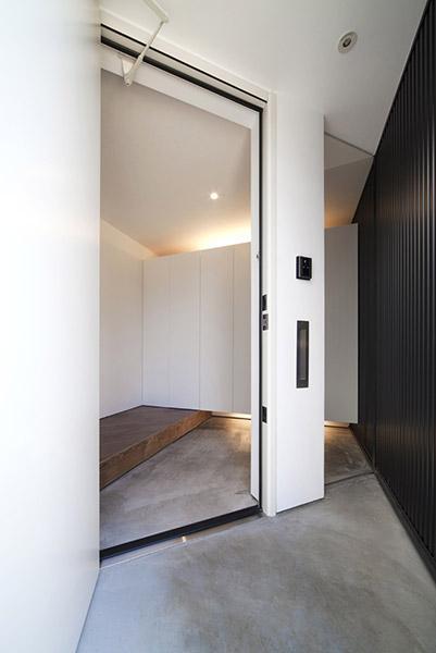 『浅間町の家』黒と深みのある木目が調和する落ち着きのある空間の写真 モノトーンの玄関ホール