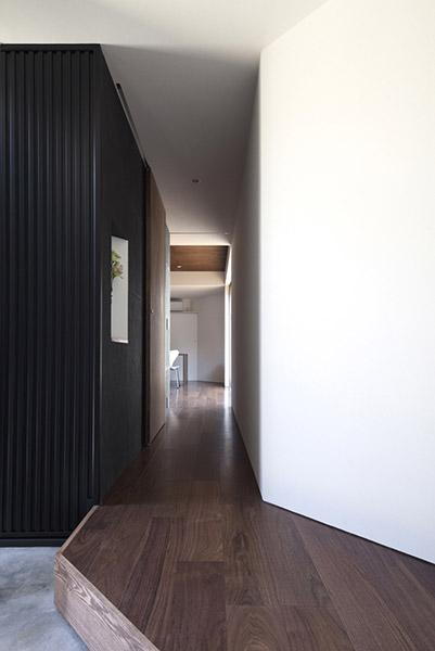 『浅間町の家』黒と深みのある木目が調和する落ち着きのある空間の写真 リビングにつながる廊下