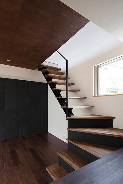 『浅間町の家』黒と深みのある木目が調和する落ち着きのある空間の写真 黒×木目調のスケルトン階段