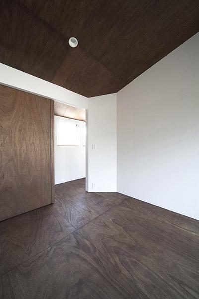 『浅間町の家』黒と深みのある木目が調和する落ち着きのある空間の写真 白×深みのある木目の寝室
