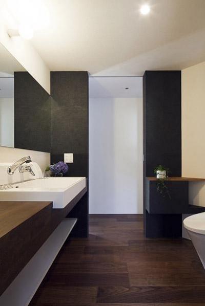 落ち着きのあるトイレ空間 (『浅間町の家』黒と深みのある木目が調和する落ち着きのある空間)
