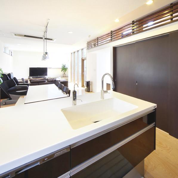 N邸・ダークブラウン基調の大人モダンな住まいの部屋 全体を見渡せる対面式キッチン