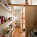 『矢来の家(減築)』過去の記憶や温もりを残す減築リフォームの写真 壁一面本棚の1階廊下