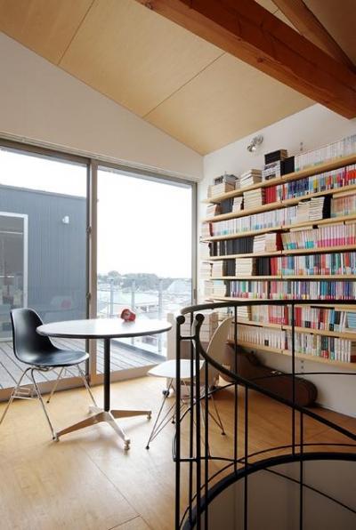 『片瀬山の家2』景色を楽しめる屋上デッキのある住まい (壁一面本棚の2階ホール)