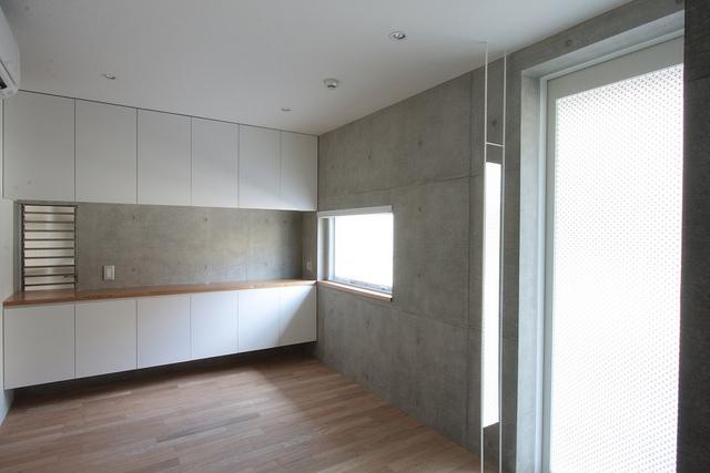 『小さな2世帯ハウス』美しく心が豊かになる玉手箱の写真 コンクリート打ち放しの洋室