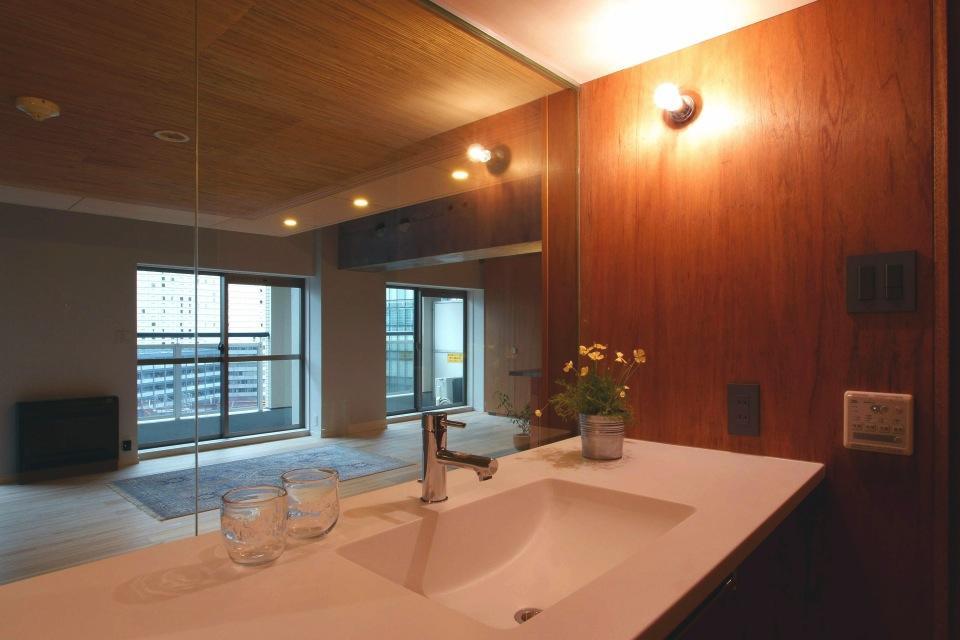 『ハイサイはうす』素材感、質感を生かすマンションリノベの写真 洗面室よりリビングを見る
