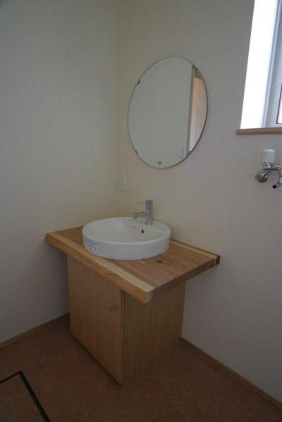 『木戸石の家』自然素材に囲まれた優しい住まい (丸鏡の洗面スペース)