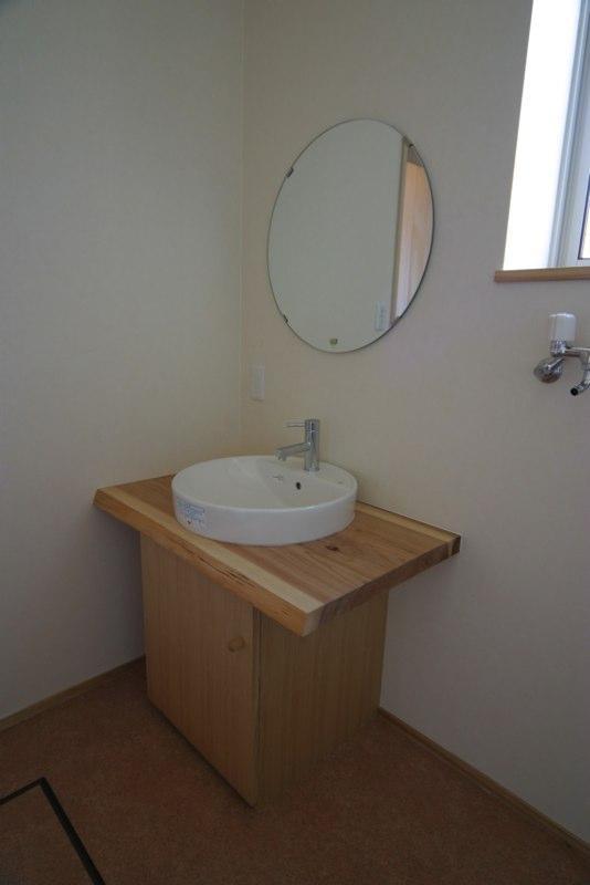 『木戸石の家』自然素材に囲まれた優しい住まいの部屋 丸鏡の洗面スペース