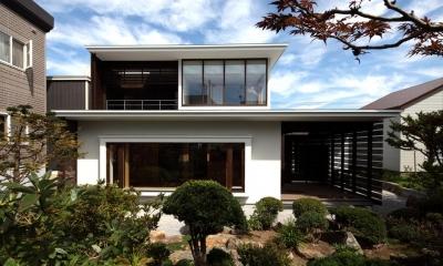 『銭函 光庭の家』質感の深みが感じられるシンプルな住まい (シンプルモダンな外観-庭側)