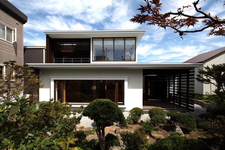 『銭函 光庭の家』質感の深みが感じられるシンプルな住まいの部屋 シンプルモダンな外観-庭側