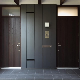 『銭函 光庭の家』質感の深みが感じられるシンプルな住まい (黒基調のシックな玄関)