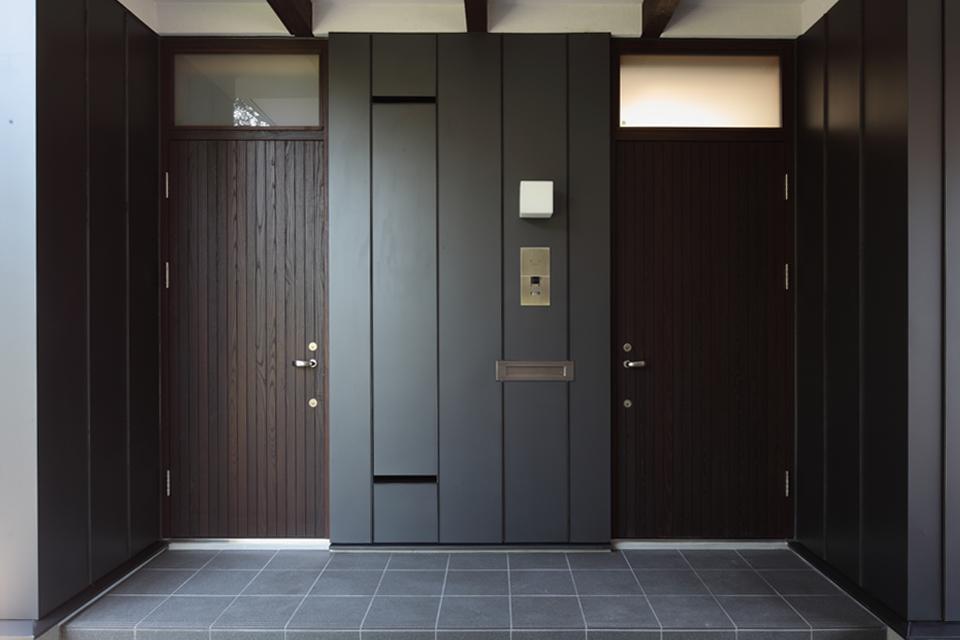 『銭函 光庭の家』質感の深みが感じられるシンプルな住まいの部屋 黒基調のシックな玄関